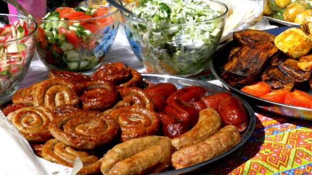 Various sausages, vegetables, Bulgarian pepper cooked on the grill lie on the counter of Street Market video