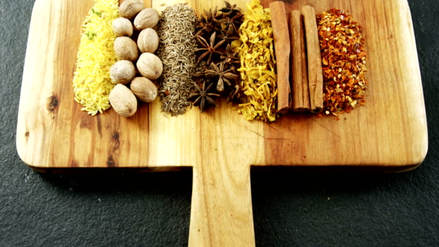Various spices arranged in row on wooden tray 4k video