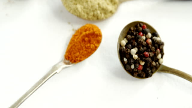 Various spices in spoon on white background 4k video