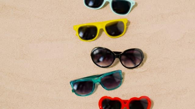 diverse sonnenbrillen am strandsand - sonnenbrille stock-videos und b-roll-filmmaterial