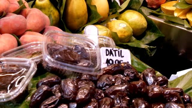 Various tropical fruits mango kiwi peaches dates on food market counter video