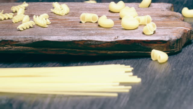 Various uncooked pasta Spaghetti, fusilli and elbows pasta on dark wood cutting board and on black table. Sliding motion uncooked pasta stock videos & royalty-free footage