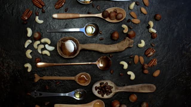 Variuos spoons with nuts and honey Assortment of wooden and metallic spoons with various nuts and honey over spotty black background. Flat dolly shot pine nut stock videos & royalty-free footage