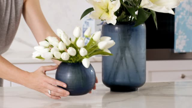 Vase of flowers A woman places a small vase of tulips next to a large vase of lilies in a clean, modern kitchen. tulip stock videos & royalty-free footage