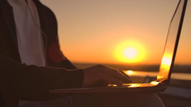 高さから街の景色を眺めながら、日没時にノートパソコンのキーボードに手入力するボールトプラン。建物の屋根に取り組むプログラマ - ウイルス対策ソフト点の映像素材/bロール