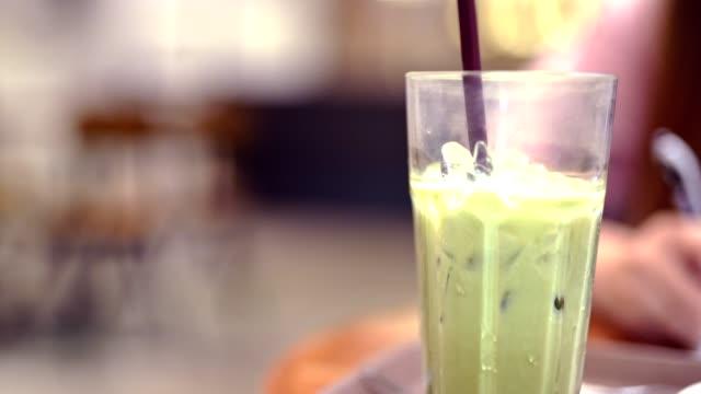 4k vdo entspannen und erfrischen lifestyle-aktivität am wochenende von mischen eis und latte grünen tee mit weichen fokus frau arbeiten in modernen coffee-shop hintergrund - grüner tee stock-videos und b-roll-filmmaterial