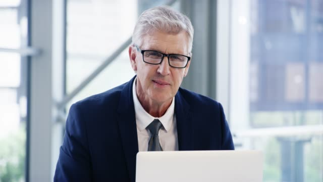 I've been leading this company for years 4k video footage of a mature businessman working on a laptop in an office happy boss stock videos & royalty-free footage