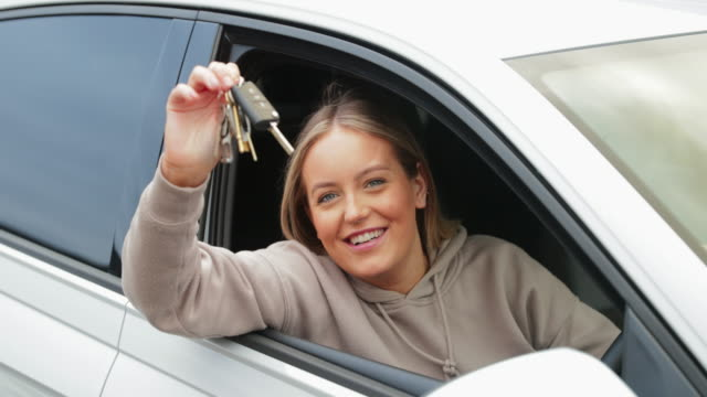 I've passed!! Hand held 4K of a Caucasian female in her 20's leaning out of a car window holding a set of car keys and looking happy as she has passed her driving test. car key stock videos & royalty-free footage