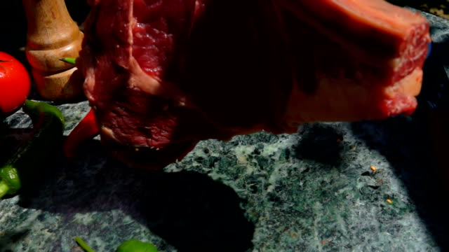 veal steak falls on a green marble table - abbrustolito video stock e b–roll