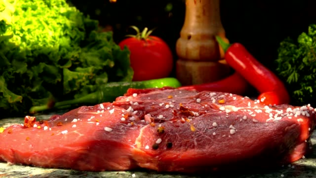 Veal steak is sprinkled with a mixture of spices Veal steak is sprinkled with a mixture of spices in slow motion roasted stock videos & royalty-free footage