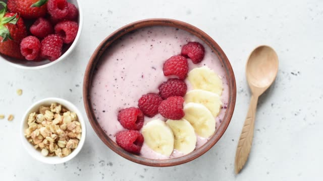 stockvideo's en b-roll-footage met veganistische acai smoothie bowl bekroond met fruit en muesli - tropisch fruit