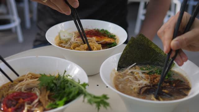 vegan asiatiska köket. sidovy av tre personer som blandar ingredienser i ramensoppa med ätpinnar - misosås bildbanksvideor och videomaterial från bakom kulisserna