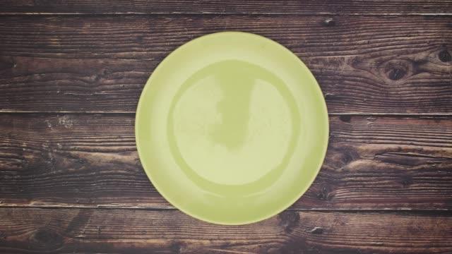 vegan ord på grön mat rätt-stop motion - empty plate bildbanksvideor och videomaterial från bakom kulisserna