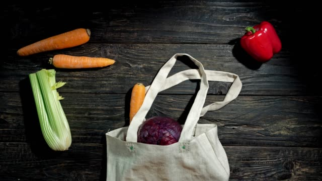 Vegetable crawling out shopping bag Vegetables are crawling out canvas shopping bag against wooden background. The bag and the vegetables are disappearing then. Animated timelapse. Vegan and raw food diet concept ingredient stock videos & royalty-free footage