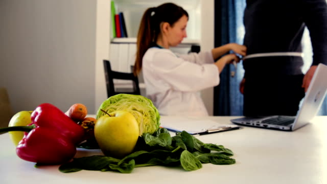 Vegetable diet nutrition and medication concept. Nutritionist measuring patients waist and advising diet plan .Nutritionists workplace Vegetable diet nutrition and medication concept. Nutritionist measuring patients waist and advising diet plan .Nutritionists workplace nutritionist stock videos & royalty-free footage