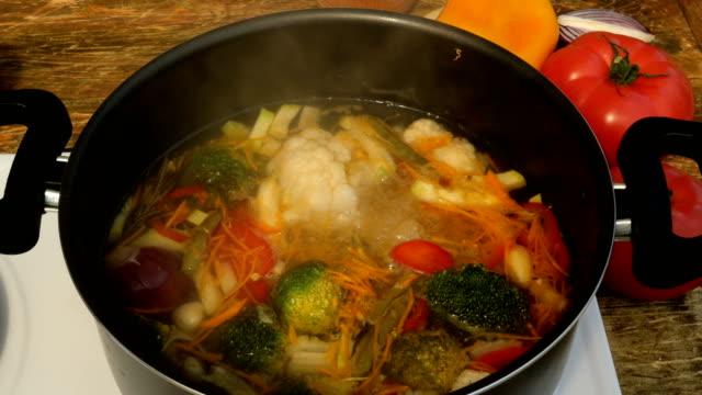 stockvideo's en b-roll-footage met groente of minestrone soep koken in een metalen steelpan op de kachel. - groentesoep