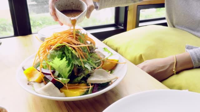 Vegetable salad and salad dressing, pouring sesame japanese dressing. Vegan food. video