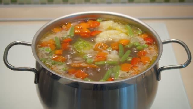 stockvideo's en b-roll-footage met de soep van de groente in een pot wordt gekookt op het fornuis - groentesoep