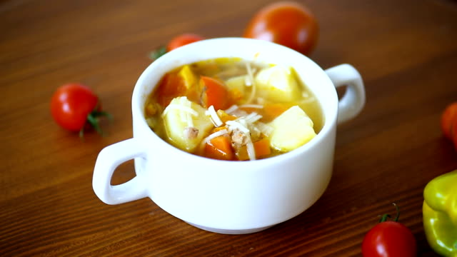 vegetable soup with noodles, tomatoes, peppers and other vegetables in a plate video