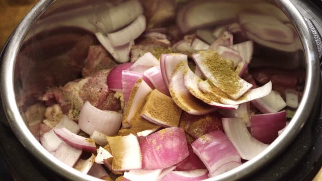 Vegetables and Seasoning in an Instant Pot Instant pot or crock pot willed with onions and veggies and spices and meat getting ready to create a home cooked meal. cooking pan stock videos & royalty-free footage