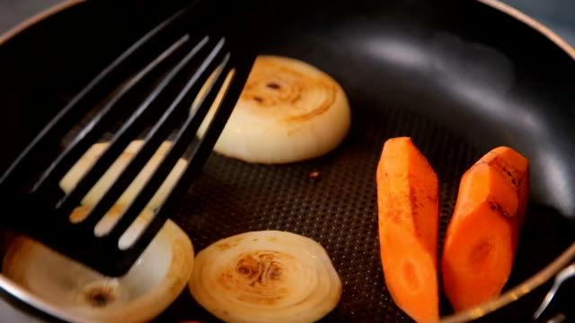 Vegetables for broth are baked in a frying pan video