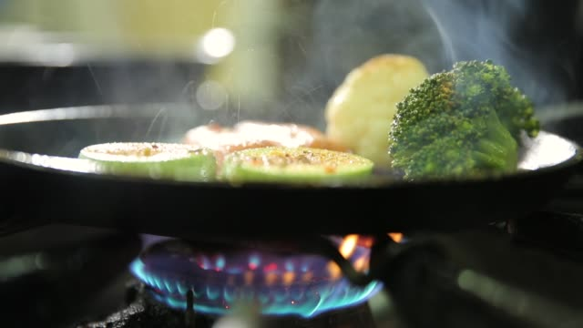 Vegetables on frying pan, gas stove