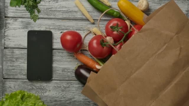 stockvideo's en b-roll-footage met groenten spinnen in de buurt van smartphone en boodschappen. vegetarisch concept - bovenkleding