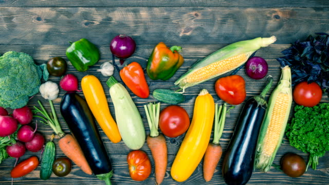 Vegetables. Stop motion. Animation Vegetables: pepper, broccoli, tomatoes, garlic, cucumber, corn, onions, celery, radishes, zucchini, carrots, eggplant, parsley, colored beans, and a stethoscope move on a wooden background.Stop motion celery stock videos & royalty-free footage