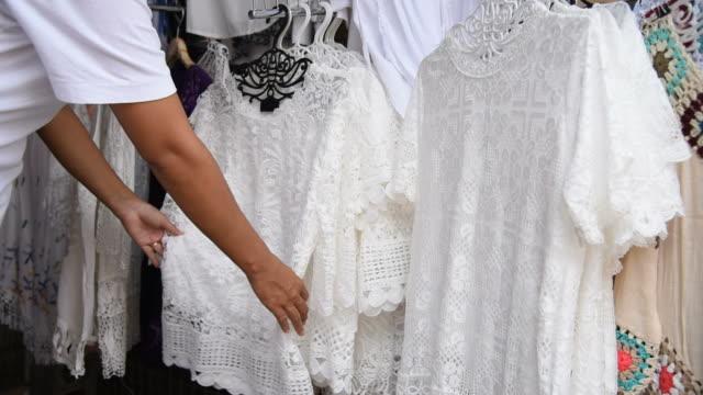 Vegetarian female choosing a white clothes for vegetarian festival in Thailand.