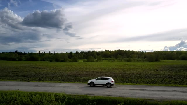 vehicle drives along old asphalt road under pictorial clouds sport utility vehicle drives along old damaged asphalt road under pictorial clouds round aerial motion. Concept road destruction and speed cars stock videos & royalty-free footage