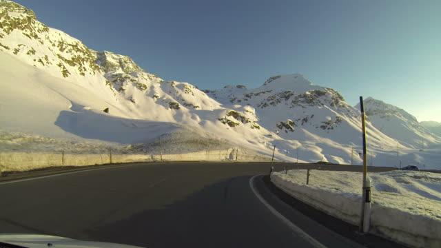 veicolo pov guida su strada di montagna neve al tramonto - passo montano video stock e b–roll