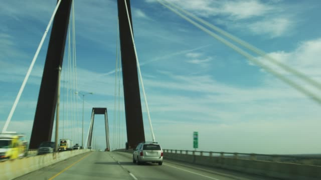 vehicle point of view of crossing hale boggs memorial bridge (suspension bridge) on interstate 310 over the mississippi river near baton rouge in southern louisiana under a partly cloudy sky - cavo d'acciaio video stock e b–roll