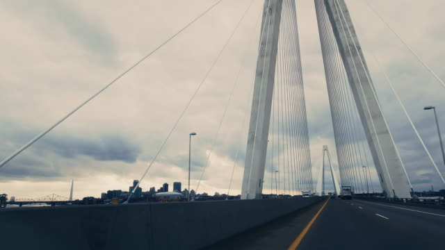 vehicle point of view of crossing the mississippi rivercrossing while traveling westbound on stan musial veterans memorial bridge (suspension bridge) on interstate 70 near st. louis, missouri and the missouri/illinois state border under a dramatic, stormy - st louis filmów i materiałów b-roll