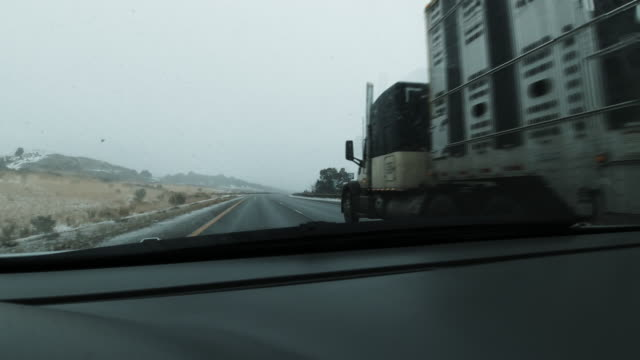 Vehicle Point of View Shot of Passing a Semi-Truck in the Passing Lane and Merging into the Right Lane on Interstate 70 on a Snowy Day in Winter