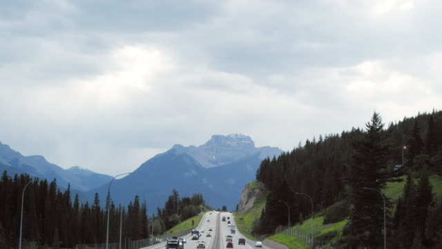 Vehicles Drive along the Trans-Canada Highway under an Overcast Sky with Forests and the Canadian Rockies in the Background in Alberta, Canada