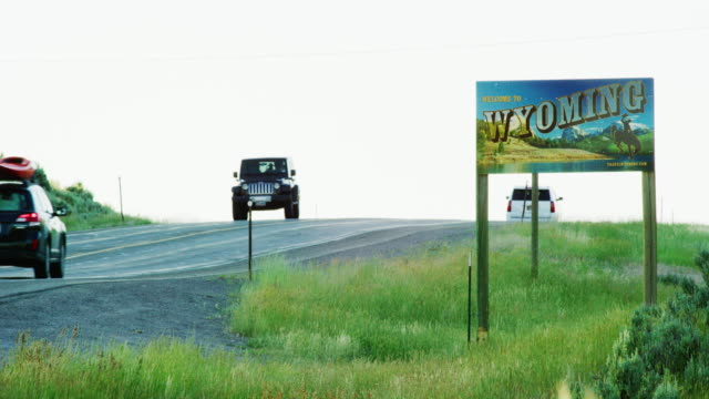 Vehicles Drive by the Wyoming State Line Sign on the Wyoming/Colorado Border at Sunset