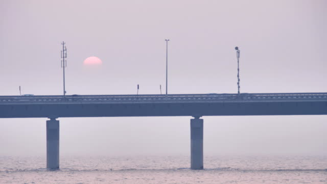 Vehicles passing on a modern bridge while sun is setting in the background video