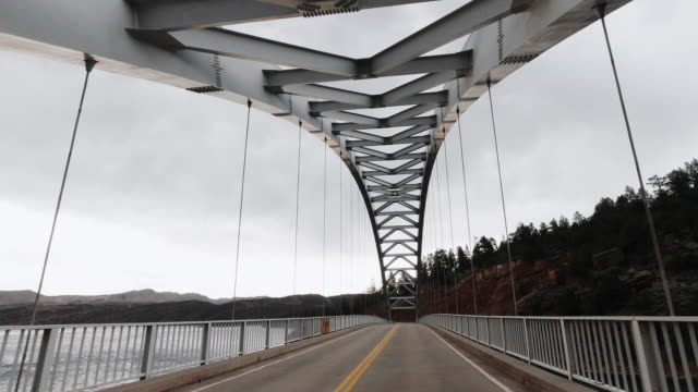 A Vehicle's Point of View Shot of Driving Across Cart Creek Bridge at Flaming Gorge in Utah under an Overcast Sky