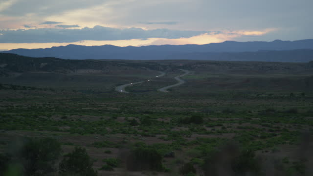 Vehicles with Headlights On Drive on Interstate 70 through the High Desert of Western Colorado at Dusk under a Dramatic Sky