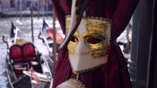 Venetian carnival mask decorated with gold with grand canal and gondolas on background in Venice. Romantic Venice video
