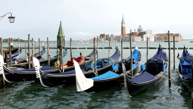 VENICE, ITALY, SEPTEMBER 7, 2017: Venetian gondola covered in blue cloth while docking on the canal in Venice Italy, Noses moored gondolas, Grand Canal, the Cathedral of San Giorgio Maggiore video