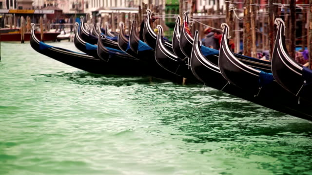 Venetian gondolas moored rocking on the green waves of the channel video