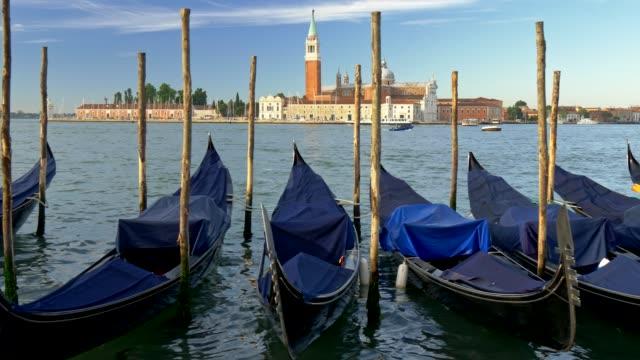 Venedig, Italien. Klassischer Blick auf die Gondeln in Venedig auf dem Markusplatz mit der Kirche San Giorgio di Maggiore im Hintergrund. Gimbal shot, 4K, UHD – Video