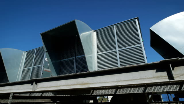 Ventilation system on the roof of an industrial building. Clearing the air in large spaces with the help of designs of corrugated pipes and air-conditioning inside the premises video