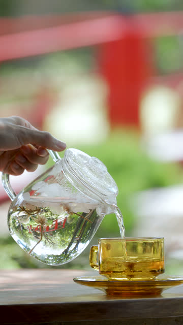 Vertical 4K Pouring Sakura Flowering Tea in Japanese garden background