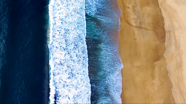 Video Vertical aerial view over a golden beach in southern France. The white waves come and go on the beach.