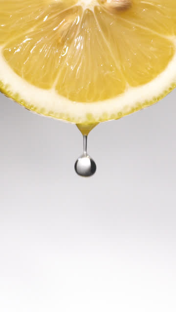 vertical and slow motion: many liquid drop from lemon slice on white - gusto aspro video stock e b–roll