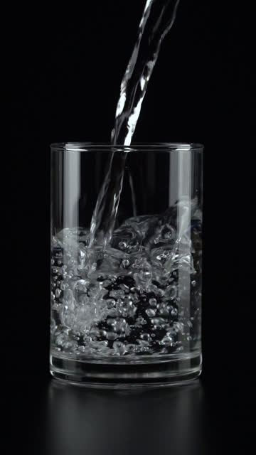 vertical and slow-motion: pouring water into a drinking glass on black background. - vertical format video stock videos and b-roll footage