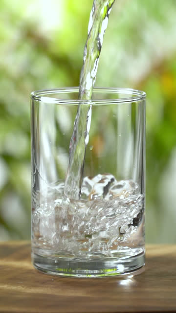 Vertical and Slow-motion: Pouring water into a drinking glass on lush foliage leaf background. Vertical and Slow-motion: Pouring water into a drinking glass on lush foliage leaf background. Concept for healthy lifestyle or purified water. purified water stock videos & royalty-free footage