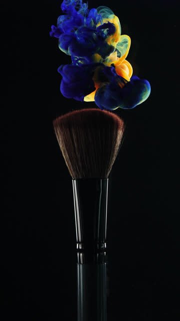 Vertical: Blue and orange ink drop falling on brush with black background in slow motion Vertical video format and 4k Orange and Blue ink drop falling on make up brush paint with black background painting art product stock videos & royalty-free footage
